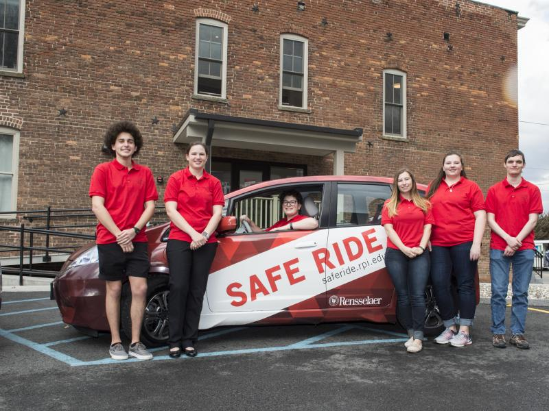 Picture of a Red Safe Ride Car and 5 Student Drivers in front